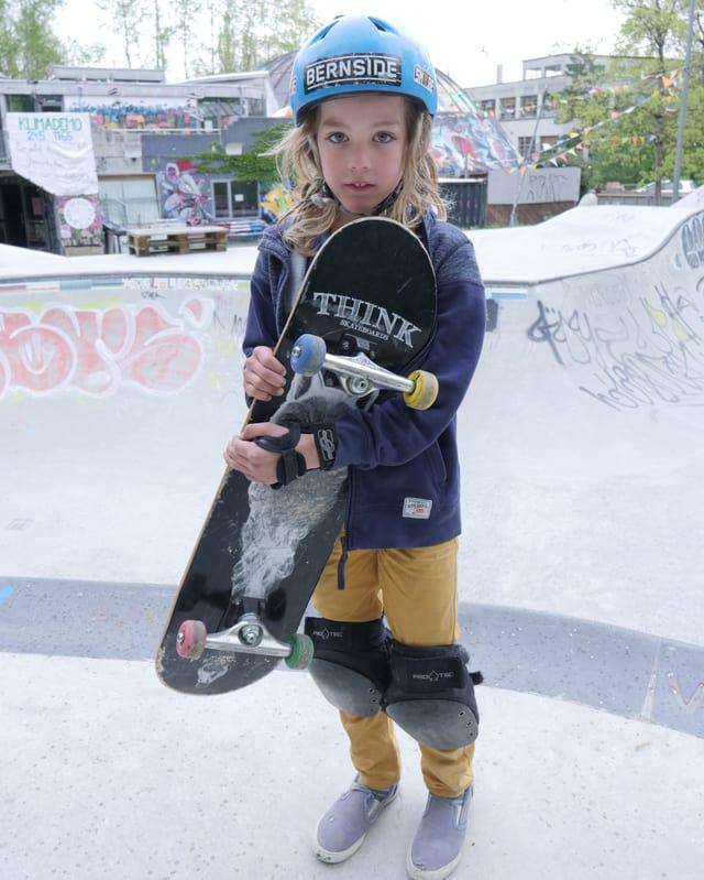 Dimitri zeigt sein Skateboard.