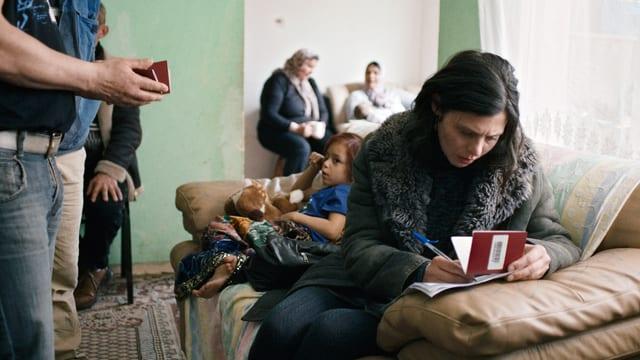 Marija füllt in einem Wohnzimmer ein Formular aus.