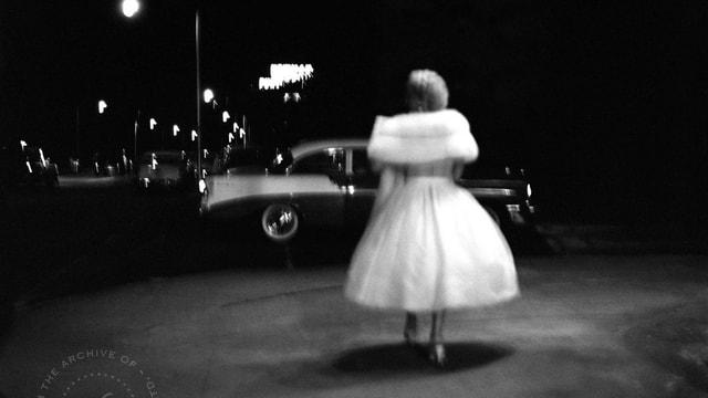 Schwar-weiss Aufnahme einer Frau in einem weissen Kleid, die über eine im Dunkel liegende Strasse spaziert.