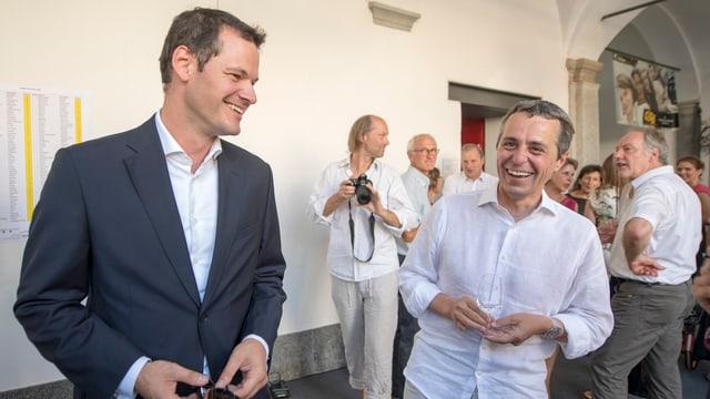 Zwei Männer, einer im Anzug, der andere in weissem Hemd.