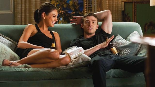 Eine junge Frau und ein junger Mann sitzen freundschaftlich auf dem Sofa und trinken Bier.