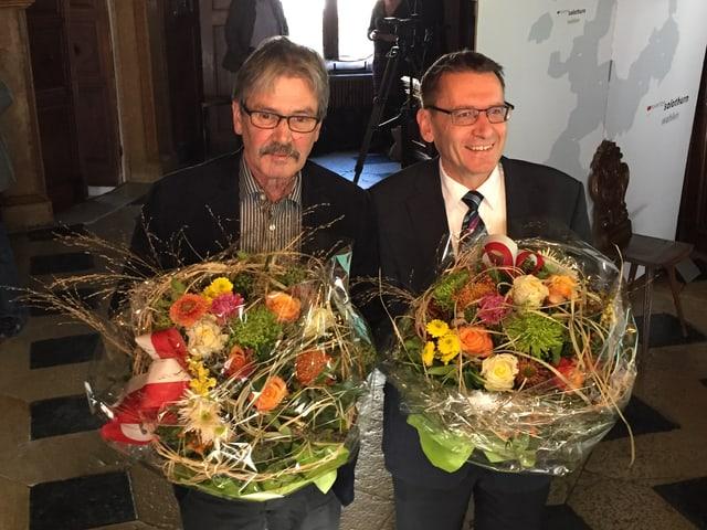 Zwei Politiker mit Blumensträussen