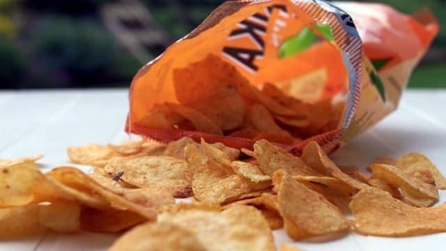 Aufgerissenes Säckli mit Pommes Chips.