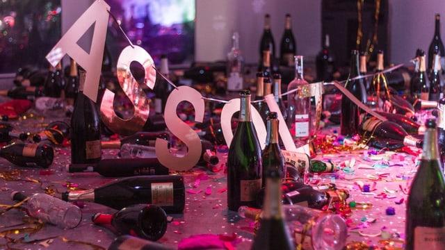 Installation mit leeren Champagnerflaschen, Partydekoration und Konfetti.