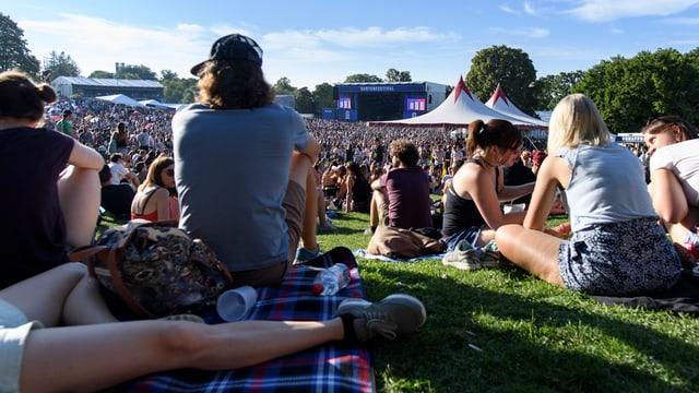 Publikum sitzt am Boden, im Hintergrund die Hauptbühne
