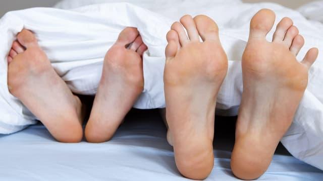 Füsse von zwei Personen nebeneinander im Bett.