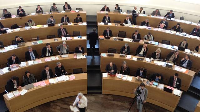Bild von der Tribüne mit Blick auf die Ratsmitglieder, die im Halbkreis im Ratssaal sitzen.