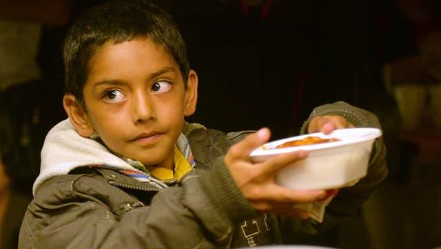 Ein Junge nimmt Essen entgegen