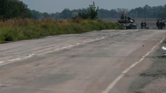 Leere Strasse in Nahaufnahme, im Hintergrund klein ein Panzer der pro-russischen Rebellen