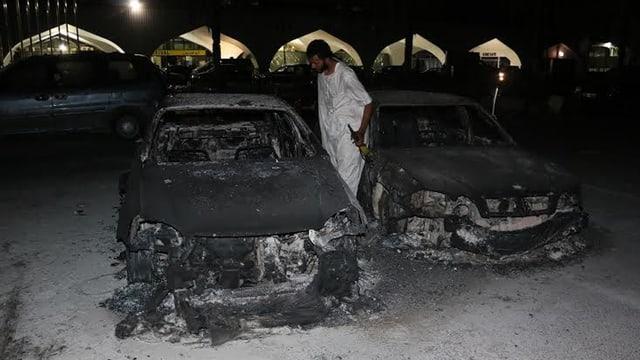 Ein bewaffneter Mann in weissem Kleid besichtigt ausgebrannte Autowracks.