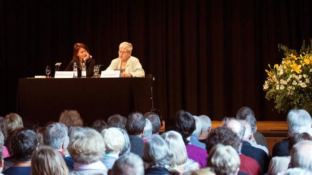 Blick vom Saal auf die Bühne, im Vordergrund Köpfe des Publikums, auf der Bühne zwei Frauen.