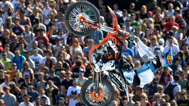 Motocross-Fahrer bei einem Sprung durch die Luft vor Menschenkulisse.