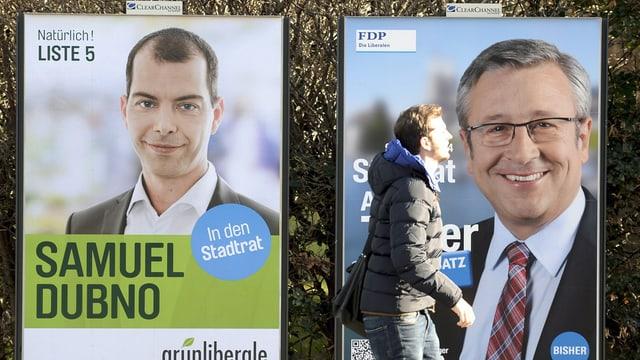 Ein Mann läuft an zwei Wahlplakaten vorbei