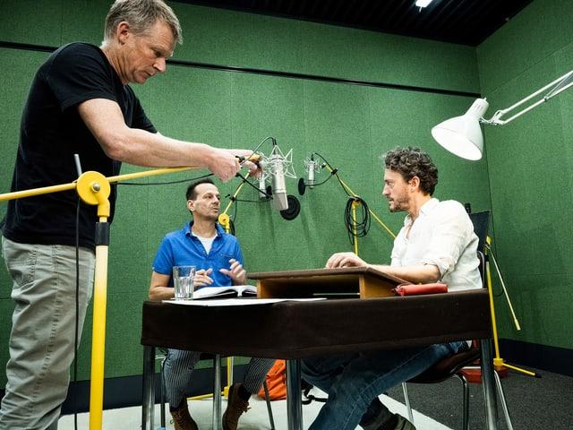 Drei Männer in einem Studio mit Mikrofonen und grünen Wänden.