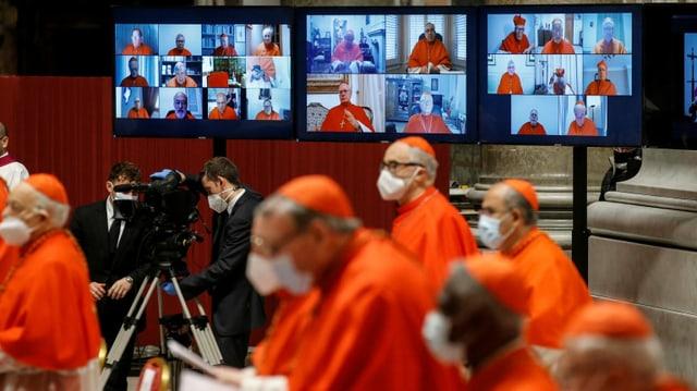 Kardinäle, im HIntergrund eine Videowand mit Bildern von anderen Kardinälen.