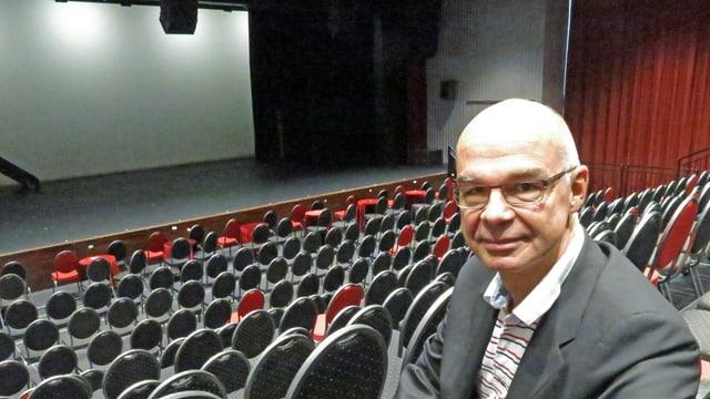 Mann sitzt in einem leeren Saal mit Bühne