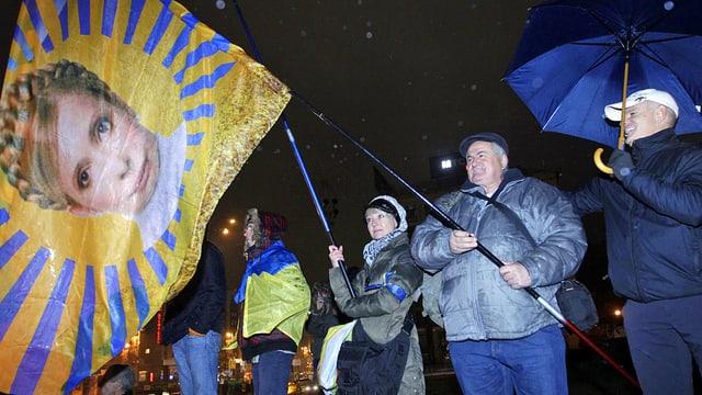 Demonstranten halten eine Fahne mit dem Bild Timoschenkos.