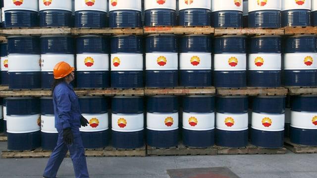 Arbeiterin geht an gestapelten Ölfässern vorbei.