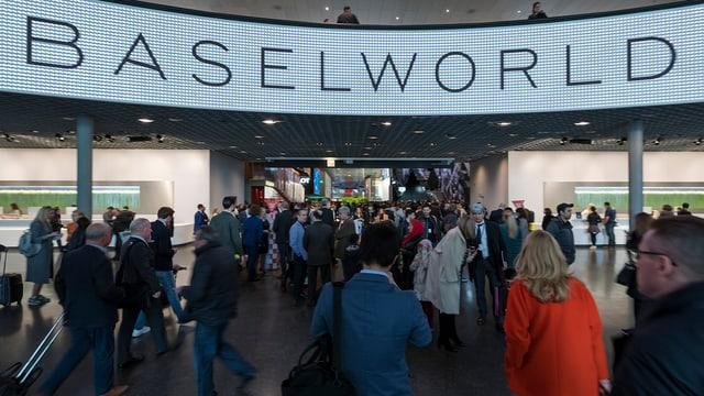 """Haupteingang der Baselworld: Man sieht ein grosser """"Baselworld""""-Schriftzug und Leute, die in die Messe gehen oder rauskommen."""