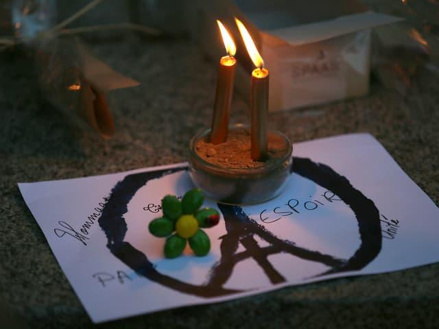 Das angepasste Peacezeichen auf dem Boden, darüber stehen Kerzen.
