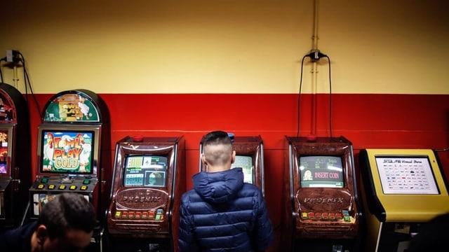 Ein Junge steht mit dem Rücken zur Kamera vor Spielautomaten.