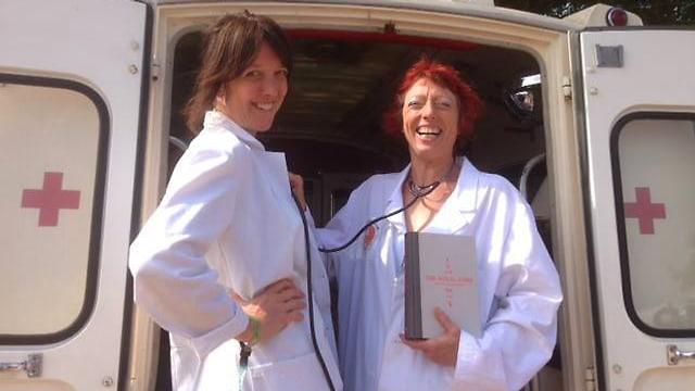 Zwei Frauen in weissen Kitteln mit einem Buch stehen lachend vor einem Krankenwagen.