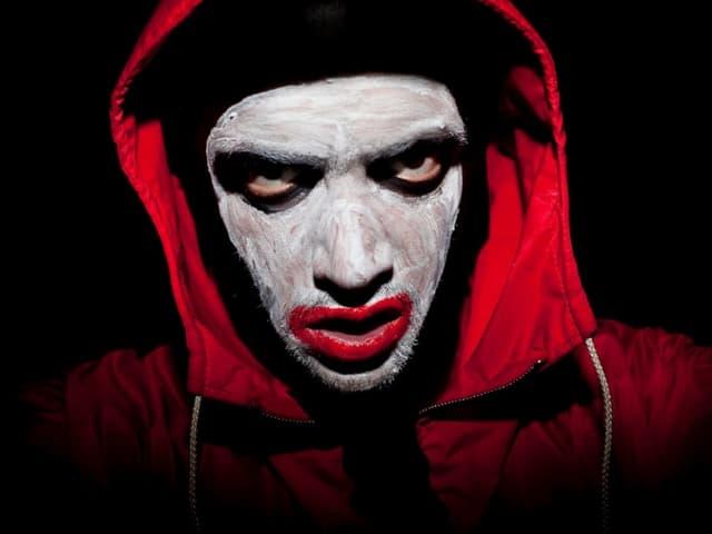 Mann mit weiss angemaltem Gesicht und rotem Hoodie.