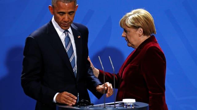 Merkel hält Obama am Arm, beide schauen ernst und etwas traurig