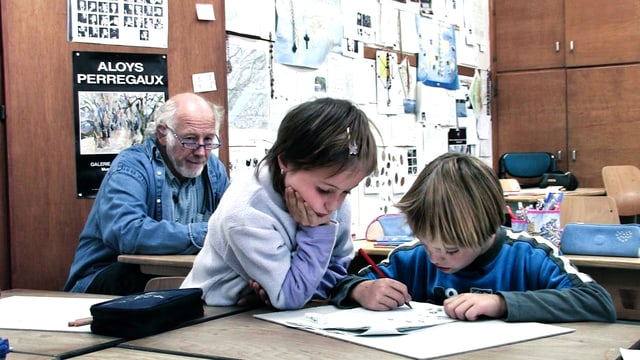 Lehrer Gilbert Hirschi im Hintergrund, zwei Schüler zeichnen im Vordergrund.