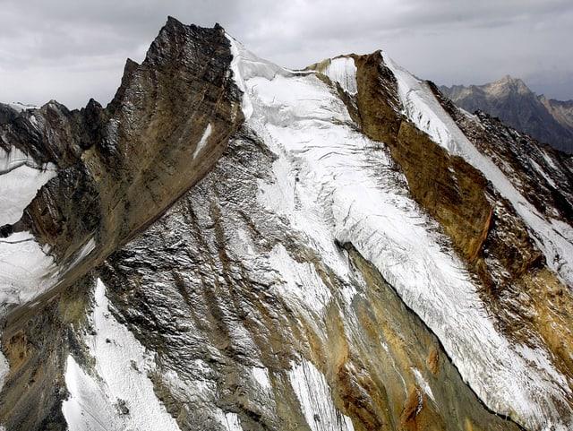 Steile Berghänge teilweise mit Schnee bedeckt aus der Luft aufgenommen.