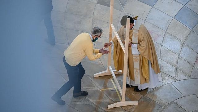 Ein Gläubiger mit Schutzmaske nimmt von einem Pfarrer hinter einer Plexiglasscheibe die Kommunion entgegen.
