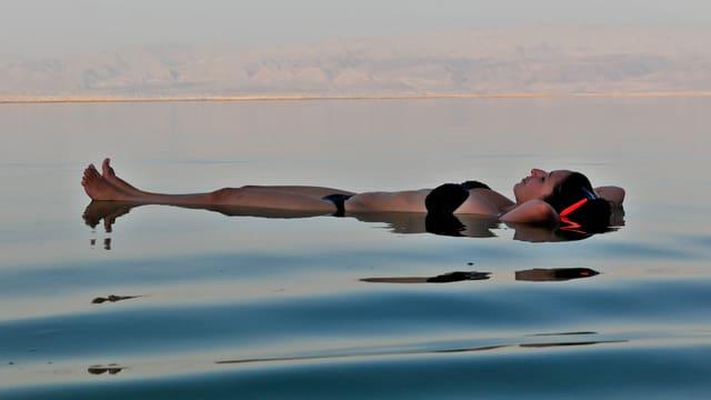Eine Frau liegt auf dem Rücken auf dem Toten Meer.
