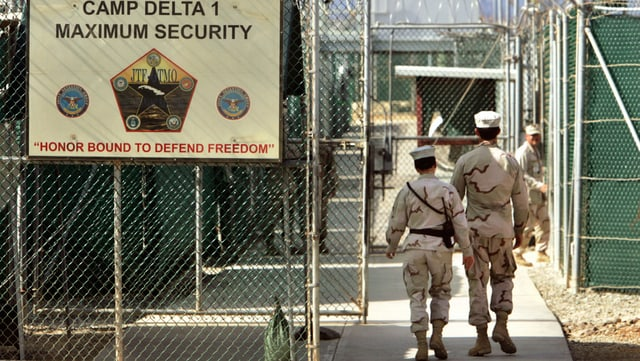 Trais survegliaders da praschun passan giatters da serrada en la praschun da Guantanamo