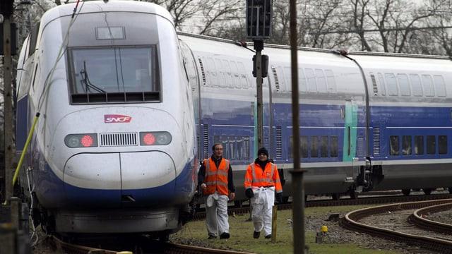 Zwei Bahnangestellte mit Leuchtwesten gehen rechts von einem stillstehendem TGV entlang.