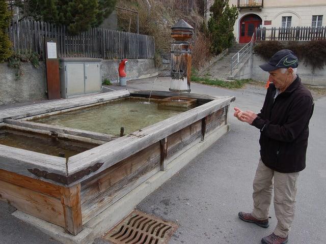 Ein Mann steht vor einem grossen Holzbrunnen.