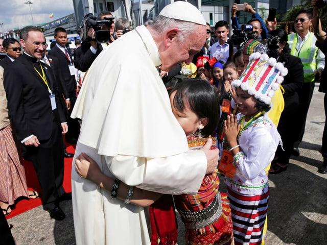Ein Kind umarmt den Papst.
