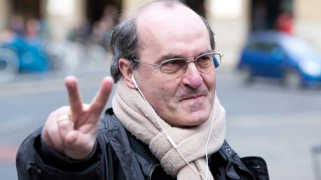 Di Stefano fotografiert auf der Strasse, macht das 'Victory'-Zeichen.