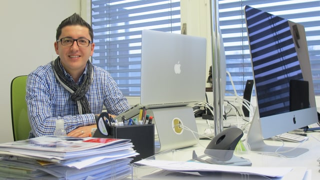 Junger Mann sitzt vor grossem Computerbildschirm in modernem Büro