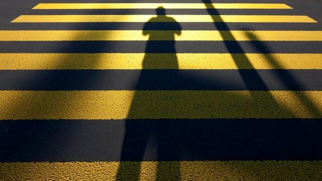 Schatten eines Menschen auf einem Fussgängerstreifen.