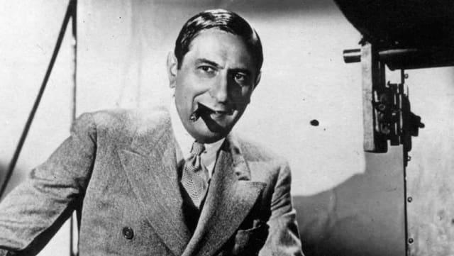 Ein Mann im Anzug mit Zigarre im Mundwinkel.