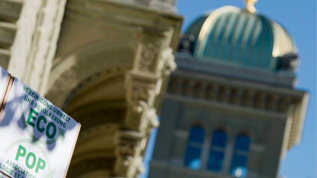 Im Vordergrund ein Ecopop-Plakat (Initiative), im Hintergrund das Bundeshaus.
