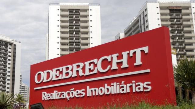 Logo des Konzerns Odebrecht vor einer Hochhaussiedlung.