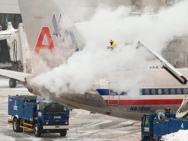 Das Heck eines Flugzeugs wird enteist. Dicke Dampfschwaden steigen auf.