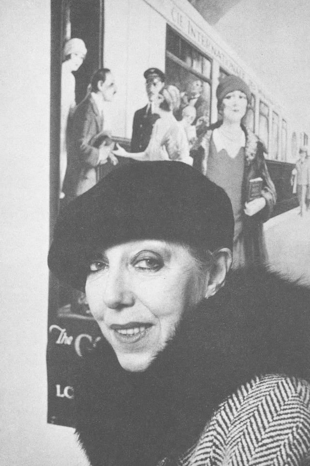 Frau mit Hut vor Bild mit Zug aus den 1920-er Jahren.