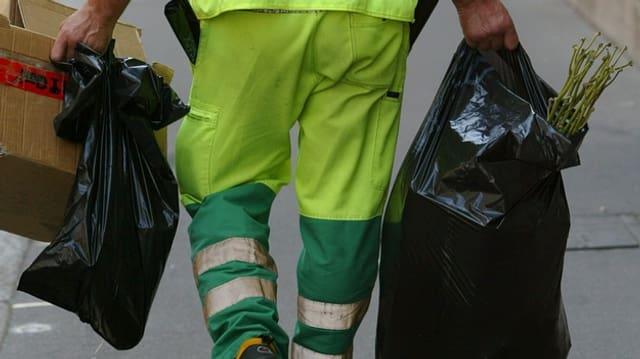 Ein Mann trägt Müllsäcke
