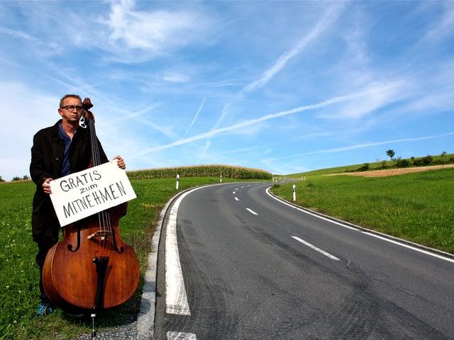 Philipp Galizia am Strassenrad mit seinem Kontrabass.