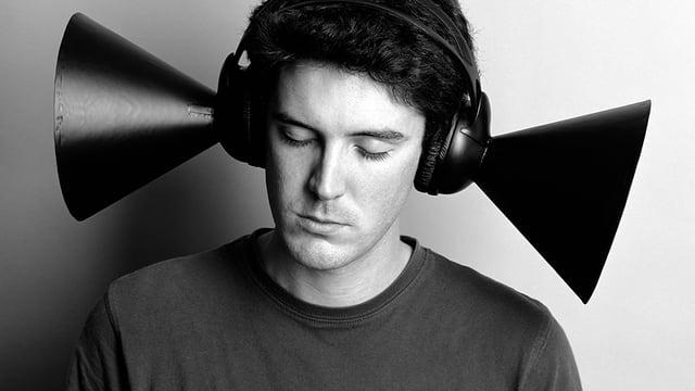 Ein junger Mann hat Kopfhörer auf, die wie Megaphone am Ohr kleben.