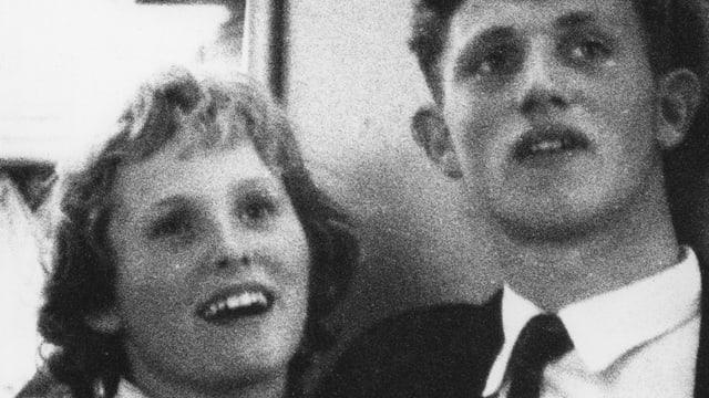 Ein Mann und eine Frau lächeln auf einem grobkörnigen SchwarzWeissbild in die Kamera.