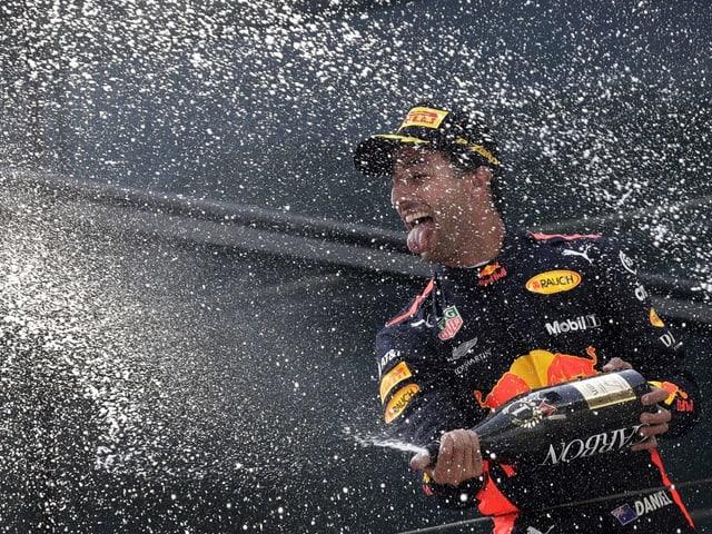 Der australische Formel 1 Pilot Daniel Ricciardo feiert seinen Sieg am GP von China mit einer Flasche Champagner.