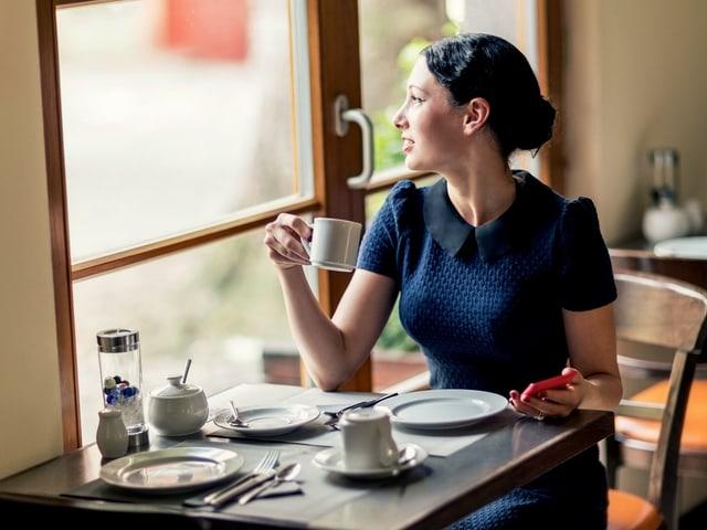 Eine Frau mit einem Smartphone an einem Kaffeetisch.